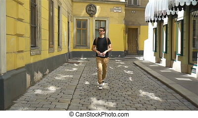 Man tourist with a city map and backpack in Europe street....