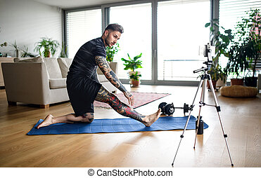 Man trainer doing online workout exercise indoors at home, using camera.