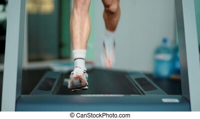 man training on a treadmill, legs, close-up