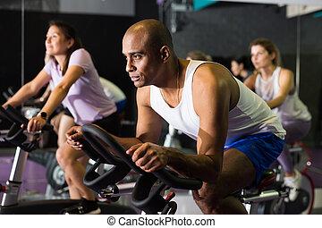 Man training on stationary bike in gym