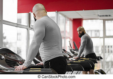 Man training on treadmill, looking at his reflection in mirror after workout
