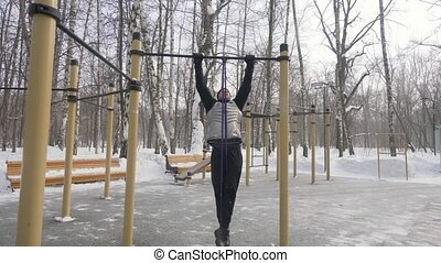 Man training pull up exercise with fitness expander on...