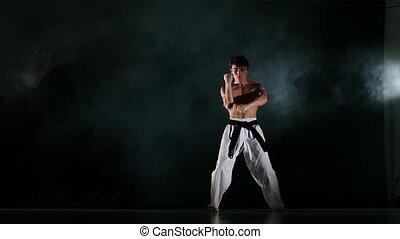 Man training taekwondo or karate Isolated on Black background. Slow motion
