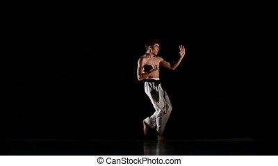 Man training taekwondo or karate jumping, high kick and fist punch Isolated on black background. Slow motion