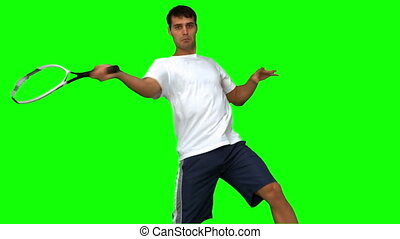 Man training while playing tennis on green screen in slow...