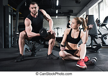 man training with dumbbell while woman holding smartphone at gym