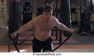 Man training with ropes during crossfit workout. Crossfit and functional training