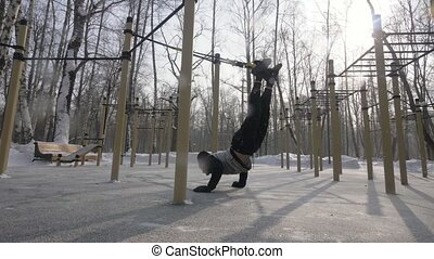 Athlete man training with sport straps on outdoor winter ground. Man using fitness equipment for crossfit training outdoor. Sport and healthy lifestyle