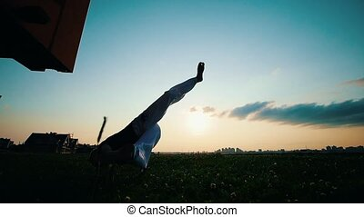 Man trains capoeira on the grass, at sunset, slow motion