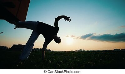 Man trains capoeira on the grass at sunset, the wind waves the flowers, slow motion
