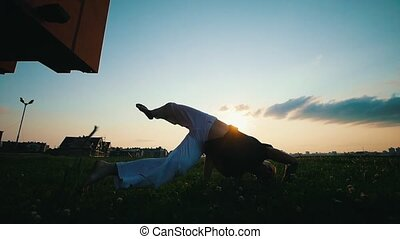 Man trains capoeira on the grass, summer warm evening, sunset, slow motion