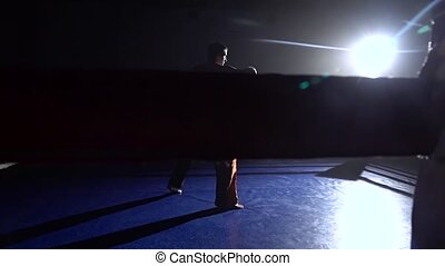Man trains in the ring . Silhouette. Light from behind