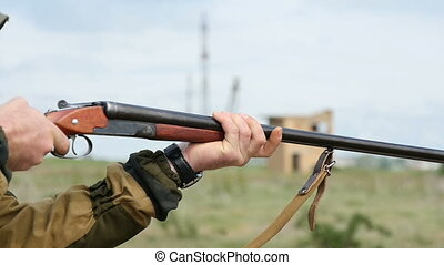 Man trains skeet shooting, while aiming somewhere from his shotgun outdoors