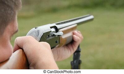 Man trains skeet shooting, while aiming somewhere from his shotgun outdoors