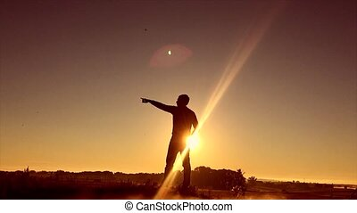 Man travel silhouette. Man shows his hand in the distance standing on a mountain silhouette sunrise sunlight