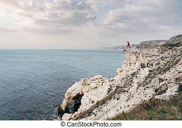 Man traveler alone on the edge of a rocky sea shore is standing with his hand up.