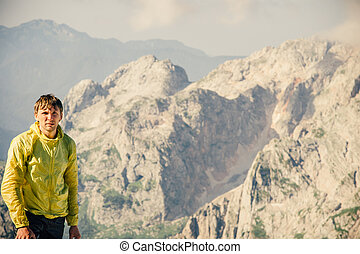 Man Traveler hiking in Mountains with beautiful summer landscape on background mountaineering sport lifestyle concept