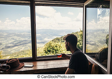 man traveler holding glass of hot tea on wooden table at window with view on mountains and sky. hipster holding drink and relaxing on mountain top. summer travel and wanderlust