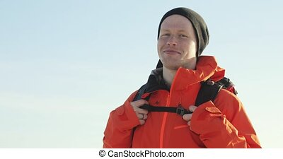Man traveler in warm clothes with backpack is looking at camera and smiling.