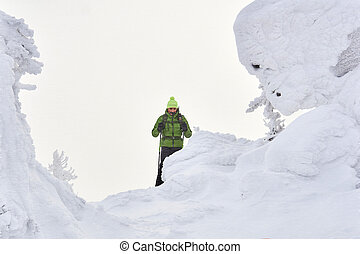 man traveler in winter mountains during a snowstorm