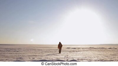 Man traveler is walking on a snow covered area in mountains, goes far away.