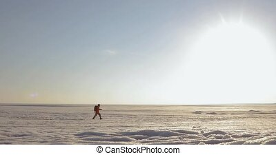 Man traveler is walking on a snow covered area in mountains. View from afar.