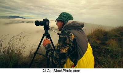 Man traveler photographer with tripod and camera taking...