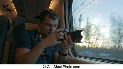 Man traveler shooting video through train window