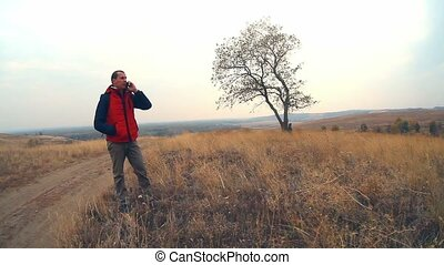 man traveler talking on the phone nature solitary tree in the fall in a red jacket travel