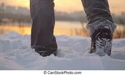 Man traveler trekking in wintertime cold snowy weather, men leg goes over natural colorful sunset sky with beautiful city background in slowmotion. 1920x1080