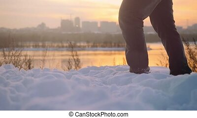 Man traveler trekking in wintertime cold snowy weather, men leg walking over natural colorful sunset sky with beautiful city background in slowmotion. 1920x1080