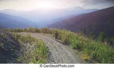 Man Traveler walking sunset mountain road