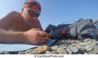 Man traveler with backpack and bicycle using smart phone on wild beach