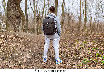 Man Traveler with backpack hiking in the spring forest, resting on the hill top. Travel and sport Lifestyle concept. Extreme vacations outdoor.