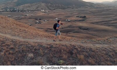 Man traveling with backpack hiking in mountains.