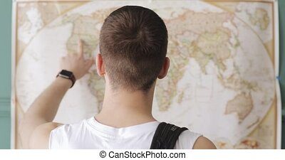 Man traveller is looking at map and pointing places to...