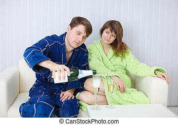 Man treats lady with champagne, at home on sofa