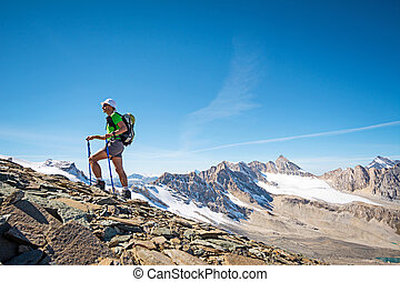 Man trekking in the Alps in a beautiful sunny day