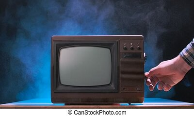 Man tries to turn on the old TV, knocks on it, scattering dust particles. Vintage television against a smoky studio background with blue neon lights. Male hands close up. Slow motion