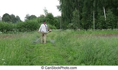 man trimmer cut grass - Man with trimmer cuts grass on...