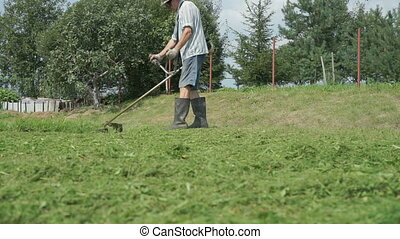 Man trimming grass in the garden using lawnmower