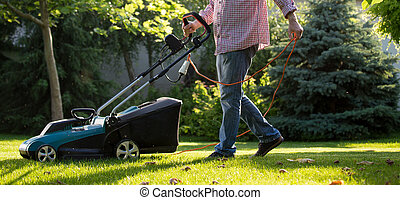 Man trimming lawn with electric mower