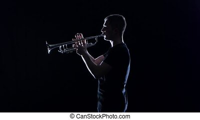 Man trumpeter blows the motif in wind instrument. Black...
