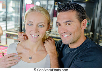 Man trying heart shaped necklace on girlfriend