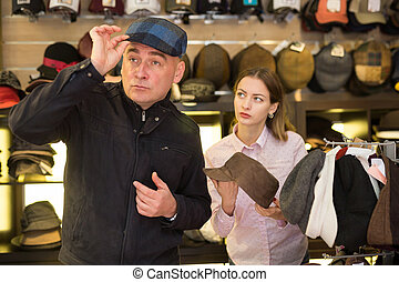 Man trying on hat in shop
