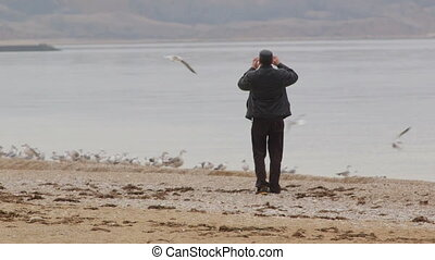 Man trying take pictures birds on the beach
