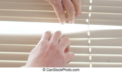 Man trying to look through the blinds on the window