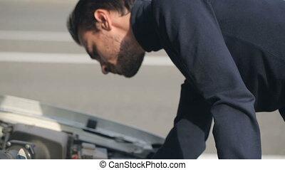 Man trying to repair a broken car