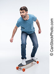 man trying to ride skateboard on white