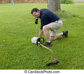 Man Trying To Start A String Trimmer - A man trying to start...
